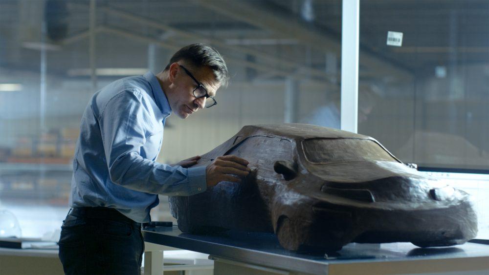 Chef-Automotive-Designer with Rake Skulptures Futuristic Car Model from Plasticine Clay