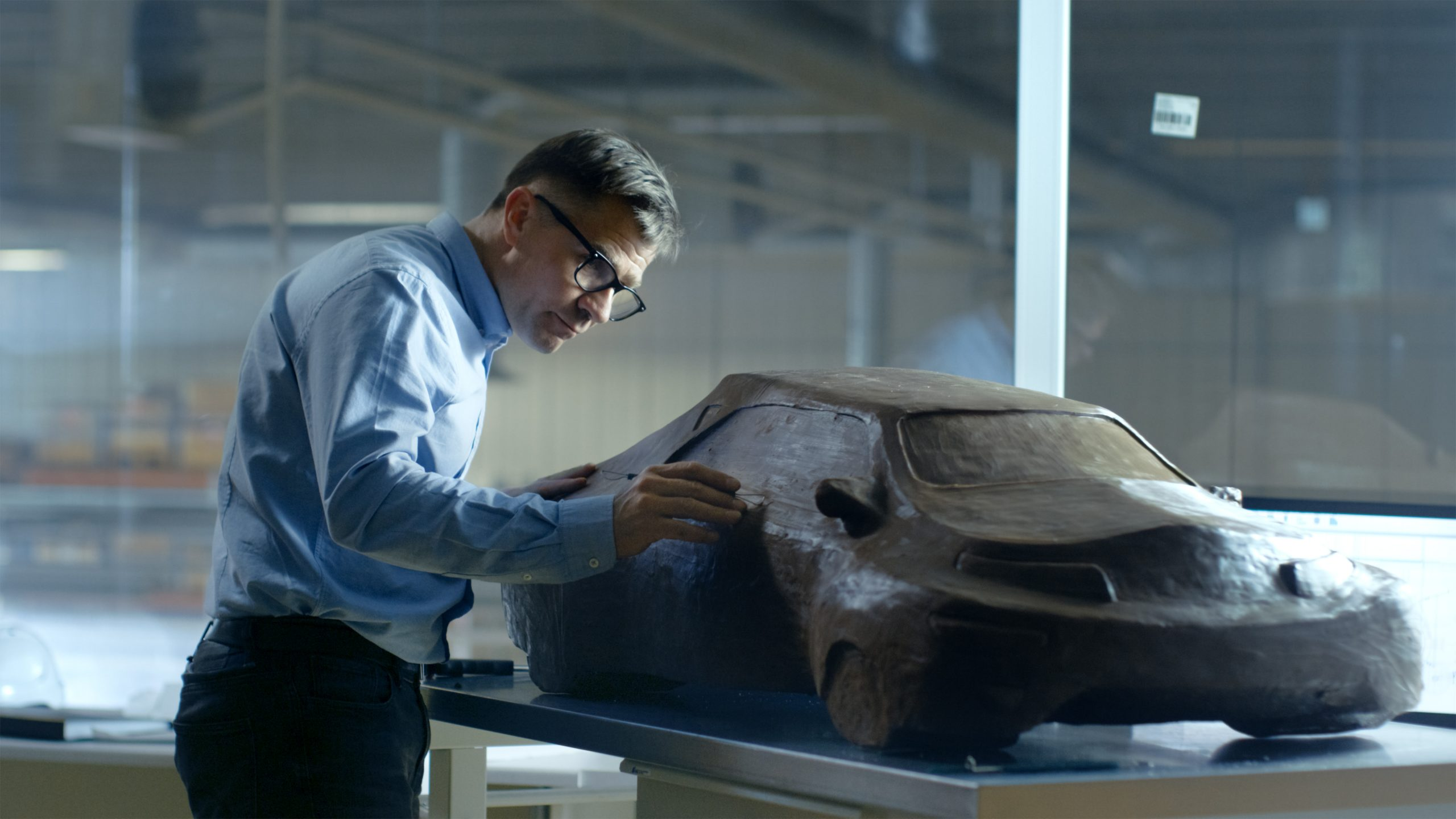 Chef-Automotive-Designer with Rake Skulptures Futuristic Car Model from Plasticine Clay
